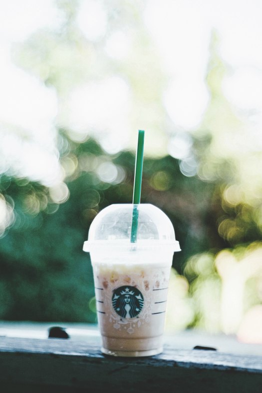 A Starbucks plastic takeaway cup and straw.